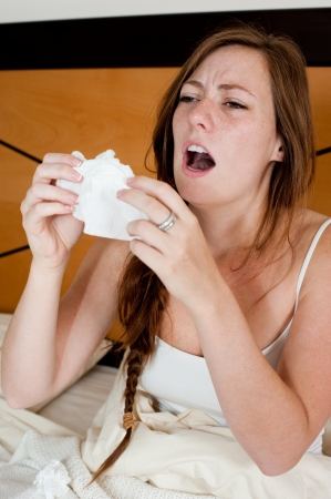 estornudo: Una mujer joven en la cama enferma, sosteniendo un pañuelo en la frente a su cara para detener un estornudo