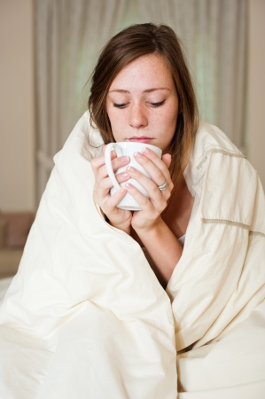 A sick young lady in bed, sitting with a blanket over her shoulders and a cup of hot beverage  photo