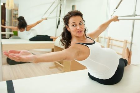 Beautiful young pregnant lady doing pilates in her last week before delivery