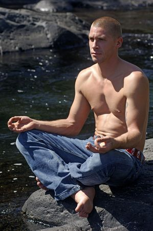Young man in zen position near a river photo