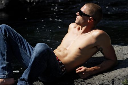 young sexy caucasian man, relaxing near a river photo