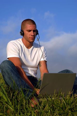 young man working on computer (with phone) in grass land photo