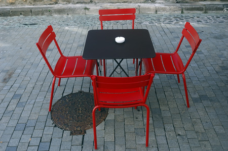 outsides: Four red bistro chairs outsides