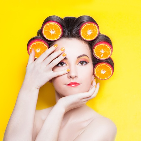 hair roller: Girl with orange slices in hair curlers on the yellow background