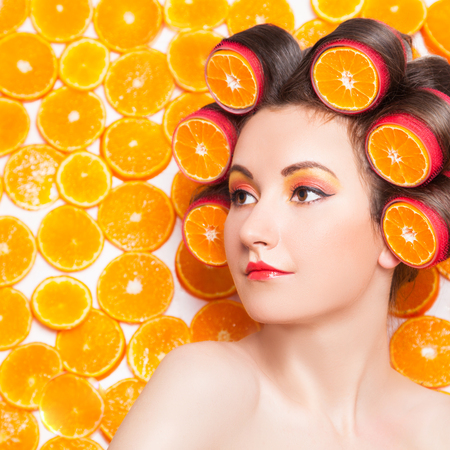 Girl with orange slices in hair curlers against fresh orange slices