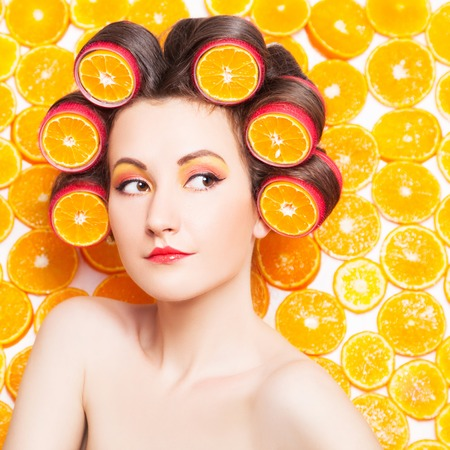 hair roller: Girl with orange slices in hair curlers against fresh orange slices