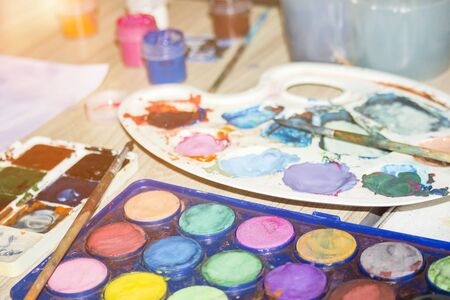 Watercolor Paints and brushes with blank white paper sheet.Watercolor paint palette.Old paint Foto de archivo