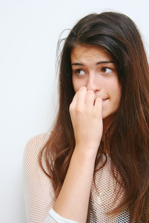 waiting glance: Nervous young lady eating her nails to the bone Stock Photo