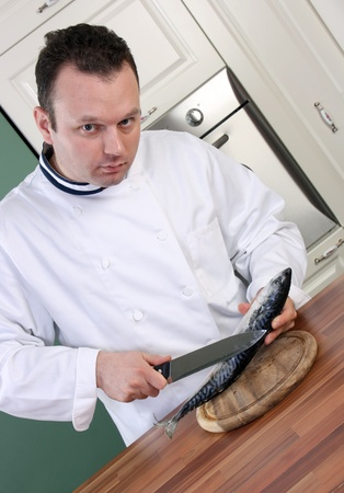 Chef starts to clean fish with big knife for cooking photo