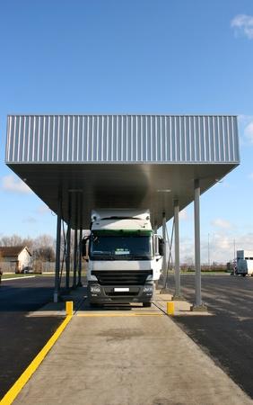 op maat: Grote witte vrachtwagen geparkeerd douane-schaal aan de grens Stockfoto