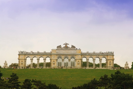 the gloriette: Gloriette of Schonbrunn palace garden with green grass and blue cloudy weather