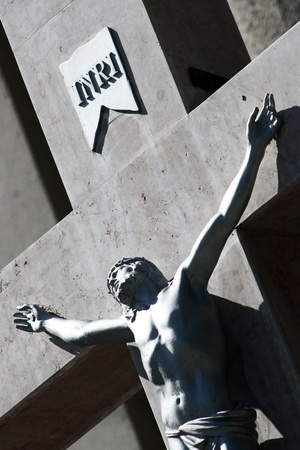 inri: Detail of Jesus on cross in front of church with letters INRI above his head