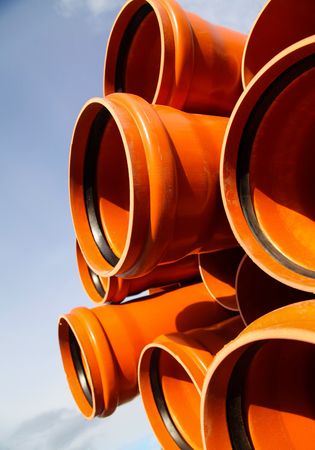 Orange plastic tubes in the stack waiting to be placed in sewerage system, and there is the blue sky too!