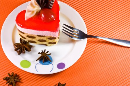 Tasty and colorful multi layer cake with chocolate decorations and red jelly.  photo