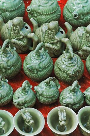 Traditional green glazed oriental ceramic teapots and cups on Chinese market bench over the red background. Stock Photo - 5856735