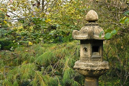 Old stone traditional lantern in the garden of oriental shrine in front of autumn foliage. photo