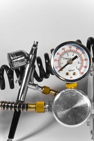 Metal shiny air brush with pressure gauge and black pipes on white background. photo