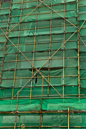 Construction scaffolding and green debris netting abstract background. photo