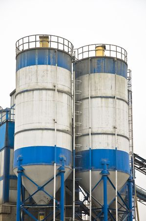 Blue and white concrete factory silos and pipeworks against white sky. photo