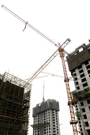 Construction site yellow tower cranes against white sky along with several skyscrappers. photo