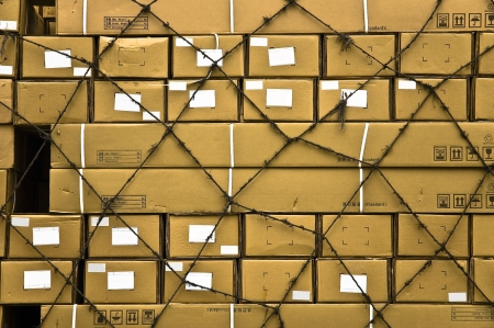 stockroom: Multiple yellow cargo boxes with white address labels covered by secure netting abstract background. Stock Photo