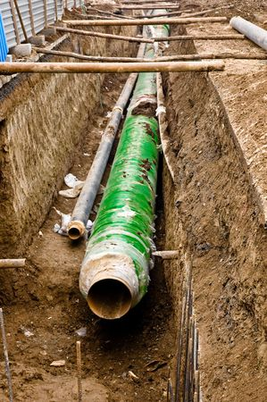 sewer pipe: Metal pipes with thick green and blue heat isolation lieing in the trench.