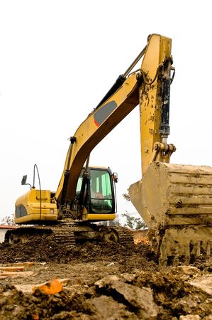 Yellow and black dirty excavator parked on the construction site. photo