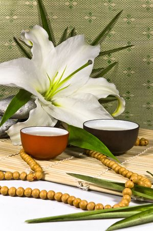 Oriental traditional tea ceremony still life - tea cups, beabs, lily flovers, stones, bamboo leafs and bamboo mat on green and white background. photo