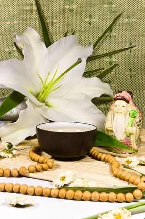 Oriental traditional tea ceremony still life - tea cup, fortune god figurine, beabs, lily flovers, stones, bamboo leafs and bamboo mat on green and white background. photo