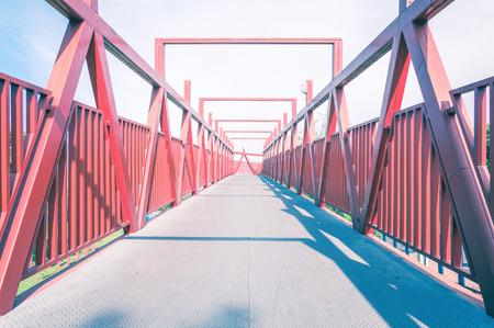 pedestrian bridges: Red bridge with metal structure. Lines in perspective, long pedestrian crossing.
