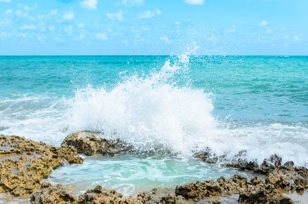 Ocean water splashing on rocks and forming a natural pool in the center of the image. Sunny day, very beautiful, with water hitting rocks and throwing many drops of water up on beach of Joao Pessoa PB, Brazil.