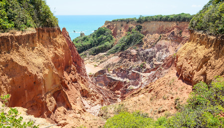 Canyon of cliffs with many stones sedimented by time, rocks with red and yellow colors and the sea in the background. Cliffs of Coqueirinho beach, PB - Brazil.