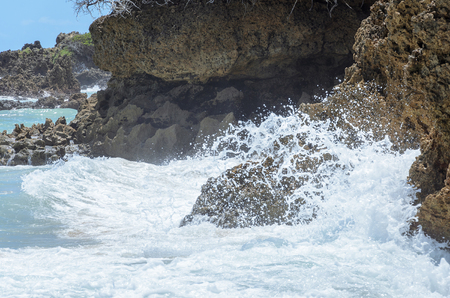Sea water hitting stones background. Rough seas in beach Coqueirinho, Joao Pessoa PB, Brazil.