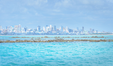 Sea with blue water with some rocks and background city. Beautiful background of coastal city, Joao Pessoa PB - Brazil.