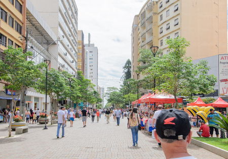 destined: Londrina, PR, Brazil - December 23, 2016: Downtown of Londrina. People walking between the downtown shops. Street called Calcadao destined to commerce and leisure.