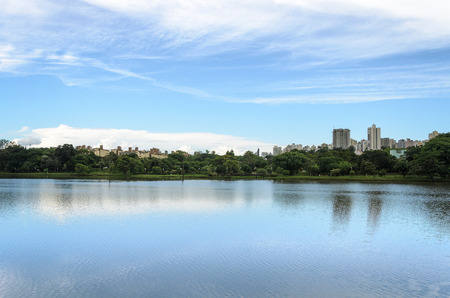 Lake reflecting on the water the city and the blue sky. Margins of the lake Igapo in Londrina, PR, Brazil. Imagens - 71795930