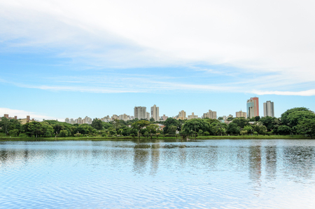 Lake reflecting on the water the city and the blue sky. Margins of the lake Igapo in Londrina, PR, Brazil. Imagens - 71795932