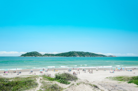 Florianopolis, SC, Brazil - December 28, 2016: People on the Campeche beach with a green water and the Campeche Island on the background on a beautiful sunny day landscape.