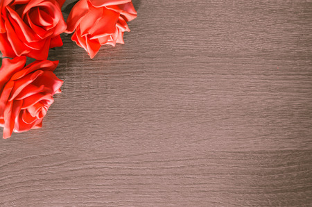 Background with some red roses on the upper left edge. Decorative background, romantic, to insert your message to the side. Stock Photo