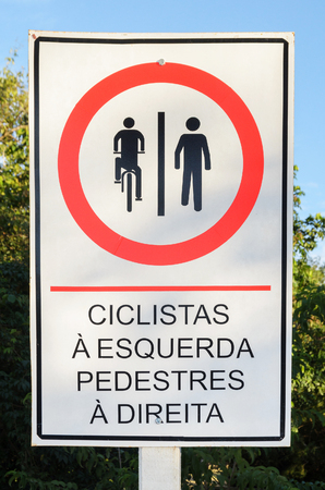 Info board in Portuguese signaling that cyclists should ride on the left and pedestrians should walk on the right. In Portuguese: ciclistas a esquerda e pedestres a direita.