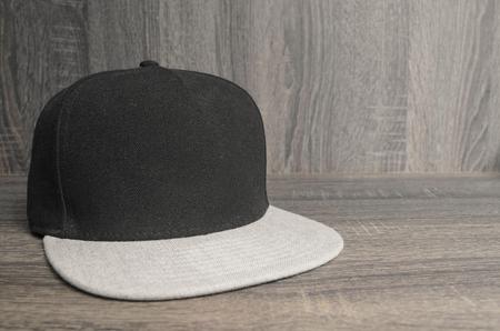 목조 배경에 밝은 회색 플랩 검은 모자. 브랜드가없는 스트레이트 플랩 캡. 측면 텍스트입니다.