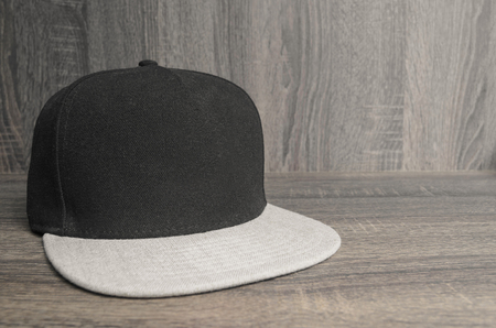 Black cap with light gray flap on a wooden background. Straight flap caps with no brand. Space for text to the side.