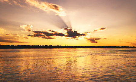 Amazing sunset at Rio Madeira in Porto Velho RO Brazil. Sunset at golden hour with some sunbeams, shadows from clouds and the reflections on the water of the river. Stock Photo
