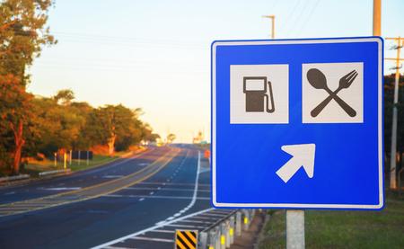 Señal de tráfico en el borde de la carretera que señala una gasolinera y servicios alimentarios en la carretera. Tablero azul con una flecha que informa servicios en línea recta.