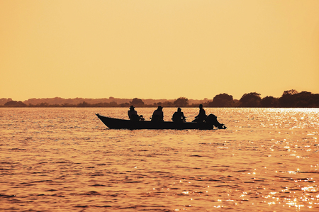 Wonderful landscape at sunset of a boat with fishermen fishing on Pantanal waters. The boat silhouette surrounded by water and nature. Photo at golden hour in Pantanal, Brazil.