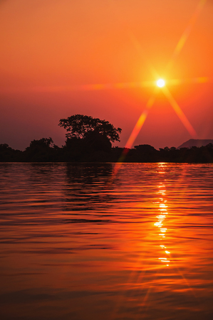 Amazing sunset at Paraguai river in Pantanal, Brazil. The river and the sun with flares at a golden hour sunset, water reflection and silhouette of nature on background.