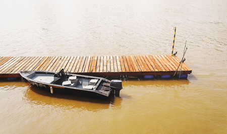 Wooden dock with a boat anchored on it. Dock in the middle of the river. Tourism or fishing background on nature.