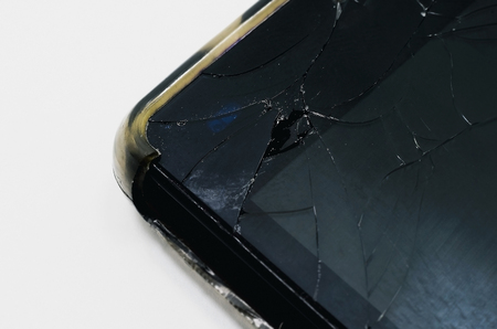 Close up on the upper corner of a smartphone with the glass broken of the screen. Stock Photo