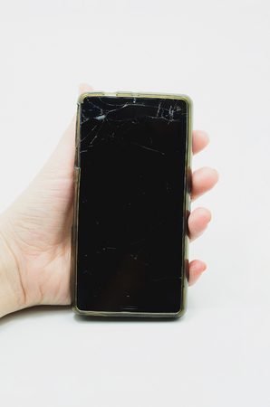 Hand holding a smartphone with the glass of the screen broken. Broken touchscreen. Stock Photo