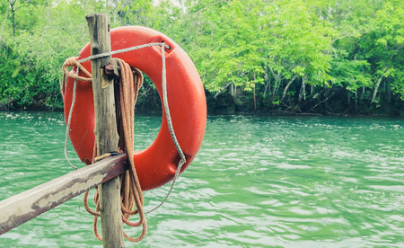 Red life buoy for safety of swimmers on the deck next to the river. Nature around, river with beautiful green water.